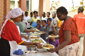 people lining up to be served with food