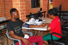 woman doing blood pressure test to another man
