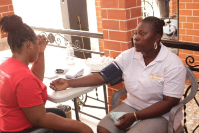 female nurse taking blood pressure test of a woman